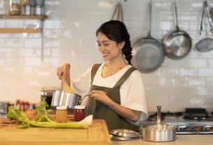 キッチンで料理を楽しむ女性の写真素材 [FYI04685929]