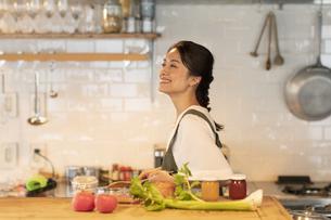 キッチンで料理を楽しむ女性の写真素材 [FYI04685931]