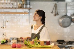 キッチンで料理を楽しむ女性の写真素材 [FYI04685932]