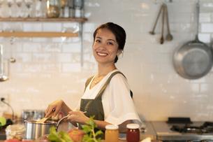 キッチンで料理を楽しむ女性の写真素材 [FYI04685933]