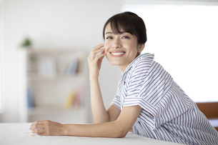 テーブルに肘をついた女性の写真素材 [FYI04685935]