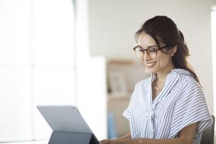 タブレットPCを操作するメガネ姿の女性の写真素材 [FYI04685938]