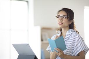 タブレットPCの前に座り手帳を持つメガネ姿の女性の写真素材 [FYI04685939]