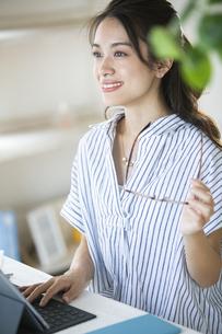 タブレットPCを操作するメガネを持った女性の写真素材 [FYI04685944]