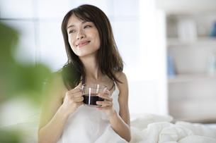 ベッドでコーヒーカップを持ち遠くを見つめる女性の写真素材 [FYI04685967]