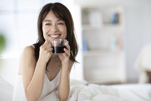 ベッドでコーヒーカップを持ち遠くを見つめる女性の写真素材 [FYI04685970]