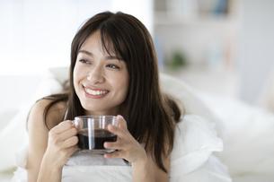 ベッドでコーヒーカップを持ち遠くを見つめる女性の写真素材 [FYI04685973]