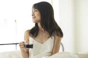 ベッドでコーヒーカップを持ち遠くを見つめる女性の写真素材 [FYI04685974]