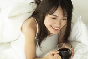 ベッドに横になりコーヒーカップを持つ女性の写真素材 [FYI04685975]