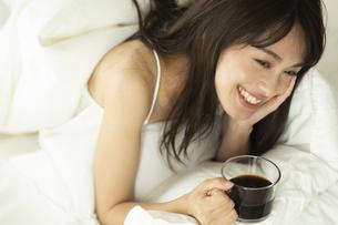 ベッドに横になりコーヒーカップを持つ女性の写真素材 [FYI04685977]