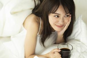 ベッドに横になりコーヒーカップを持つ女性の写真素材 [FYI04685978]
