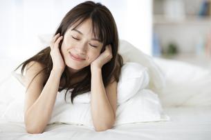 ベッドでうつ伏せで肘をつく女性の写真素材 [FYI04685984]