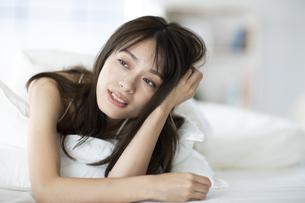 ベッドでうつ伏せで肘をつく女性の写真素材 [FYI04685985]