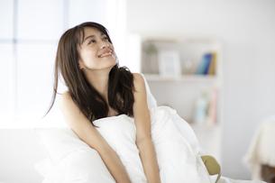 ベッドで枕を抱える女性の写真素材 [FYI04685989]