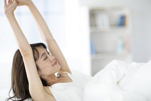 ベッドで伸びをする寝起きの女性の写真素材 [FYI04685994]