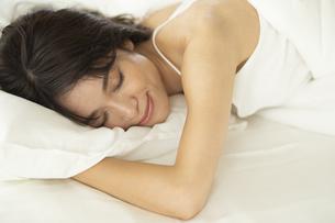 ベッドで気持ちよさそうに寝る女性の写真素材 [FYI04686001]