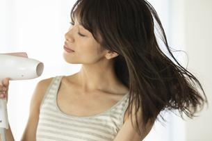 髪の毛をドライヤーで乾かす女性の写真素材 [FYI04686014]