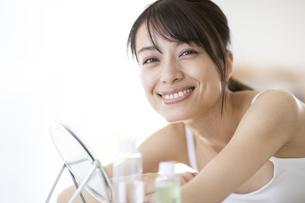 化粧品が並ぶ机に肘をのせた女性の写真素材 [FYI04686015]