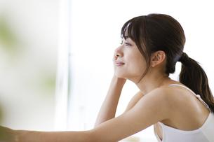 机に肘を付いて外を眺める女性の写真素材 [FYI04686016]