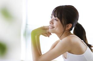 机に肘を付いて外を眺める女性の写真素材 [FYI04686017]
