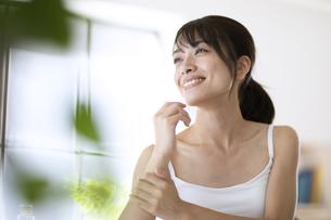 机に肘を付いて外を眺める女性の写真素材 [FYI04686019]