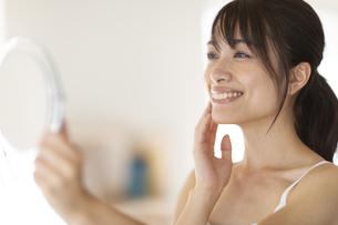 手鏡を持ち頬に手をあてた女性の写真素材 [FYI04686024]