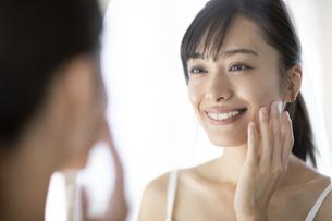 鏡の前で頬に手をあてる女性の写真素材 [FYI04686028]