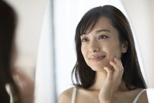 鏡の前で頬に手をあてる女性の写真素材 [FYI04686029]