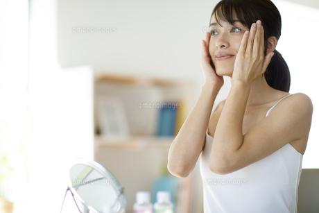 鏡の前で頬に手をあてスキンケアをする女性の写真素材 [FYI04686032]