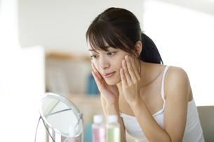鏡の前で頬に手をあてスキンケアをする女性の写真素材 [FYI04686033]