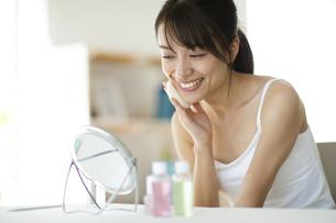 鏡の前で頬に手をあてスキンケアをする女性の写真素材 [FYI04686035]