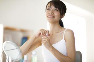 鏡の前で化粧水を開けようとする女性の写真素材 [FYI04686036]