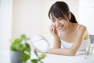 鏡の前で頬に手をあてスキンケアをする女性の写真素材 [FYI04686037]