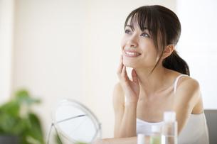 鏡の前で頬に手をあてスキンケアをする女性の写真素材 [FYI04686039]