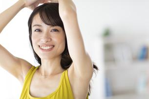 窓際で髪を結ぶ女性の写真素材 [FYI04686044]