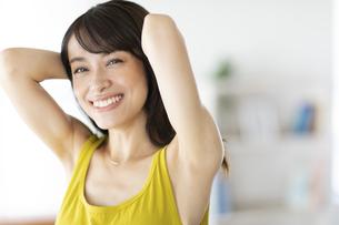 窓際で髪を結ぶ女性の写真素材 [FYI04686045]