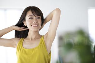 窓際で髪を結ぶ女性の写真素材 [FYI04686049]