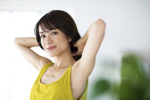 窓際で髪を結ぶ女性の写真素材 [FYI04686050]