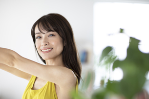 両腕をあげて微笑む女性の写真素材 [FYI04686053]