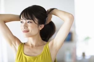 窓際で髪を結ぶ女性の写真素材 [FYI04686056]