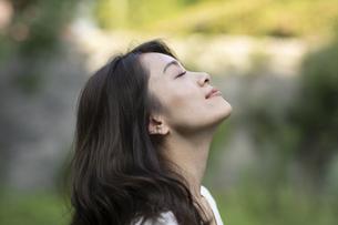 庭で外の空気を感じてる女性の写真素材 [FYI04686063]