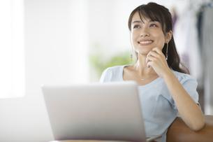 ソファーでノートパソコンを膝に乗せた女性の写真素材 [FYI04686066]