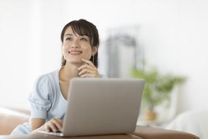 ソファーにノートパソコンを乗せた女性の写真素材 [FYI04686067]