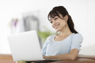 ソファーでノートパソコンを操作する女性の写真素材 [FYI04686069]