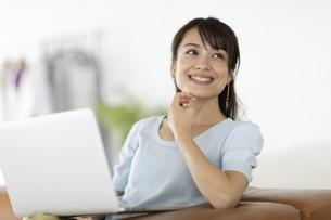 ソファーでノートパソコンを膝に乗せた女性の写真素材 [FYI04686070]