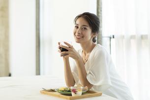 テーブルで朝食を食べようとする女性の写真素材 [FYI04686075]