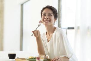 テーブルで朝食を食べようとする女性の写真素材 [FYI04686076]