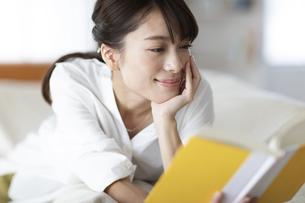 ソファーに横たわり読書を楽しむ女性の写真素材 [FYI04686078]