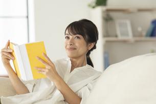 ソファーで読書をする女性の写真素材 [FYI04686079]