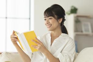 ソファーで読書をする女性の写真素材 [FYI04686080]
